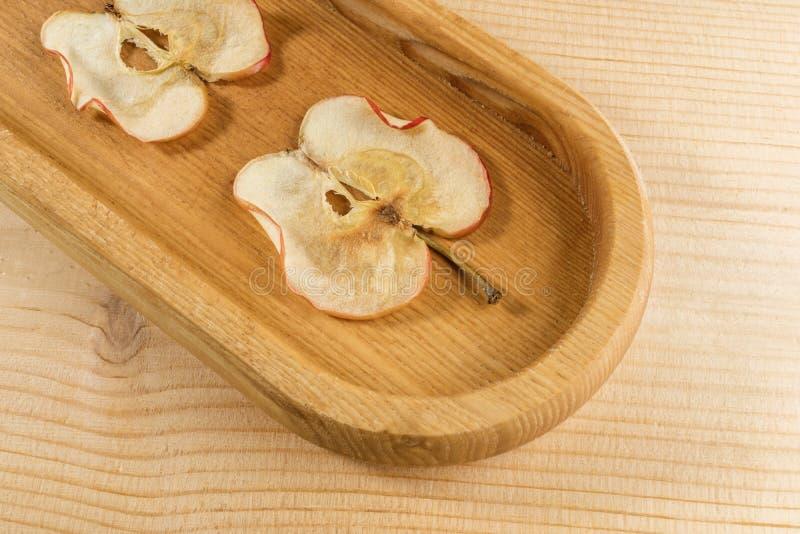 Een close-updeel van langwerpige houten plaat met appelspaanders op houten achtergrond stock foto's