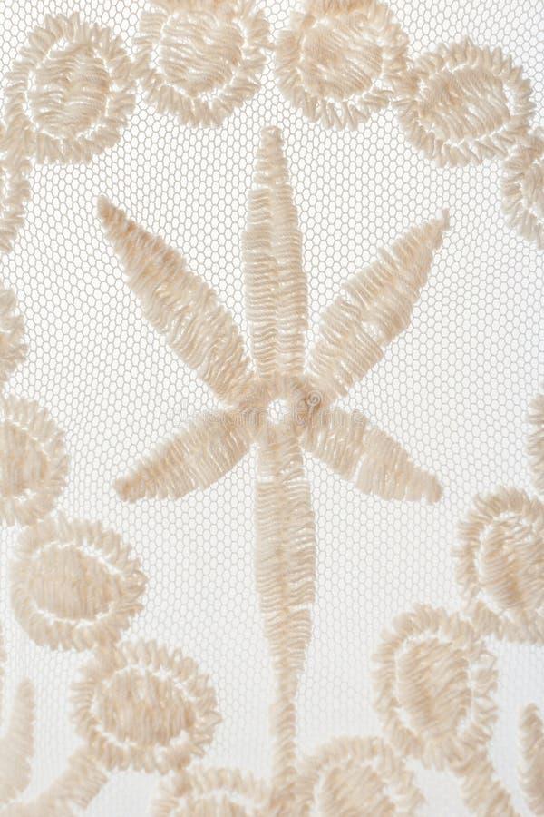 Een close-updeel van netwerk beige kant met bloemenmotief op witte rug royalty-vrije stock foto's