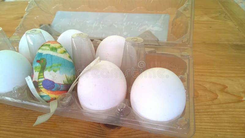 Een close-upfoto van één enkel geschilderd plastic paasei nestelde binnen van een plastic eikarton met verscheidene echte kippene stock fotografie
