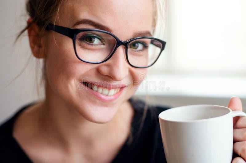 Een close-upportret die van jonge vrouwelijke student, kop van koffie houden royalty-vrije stock fotografie