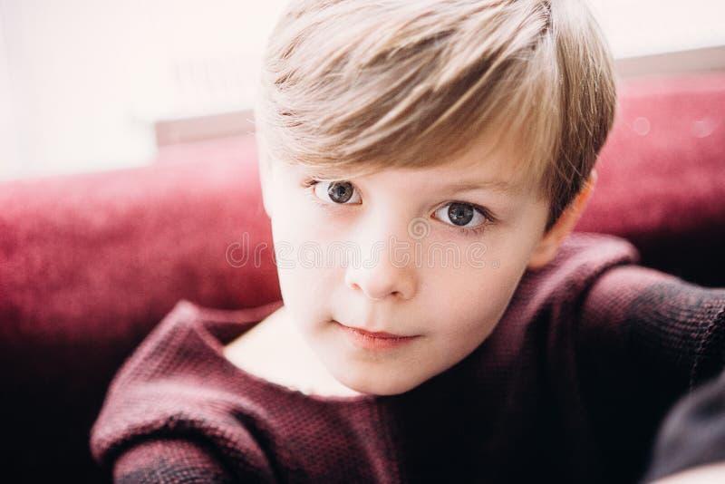 Een close-upportret van een leuke jong geitjejongen met grijze ogen stock fotografie