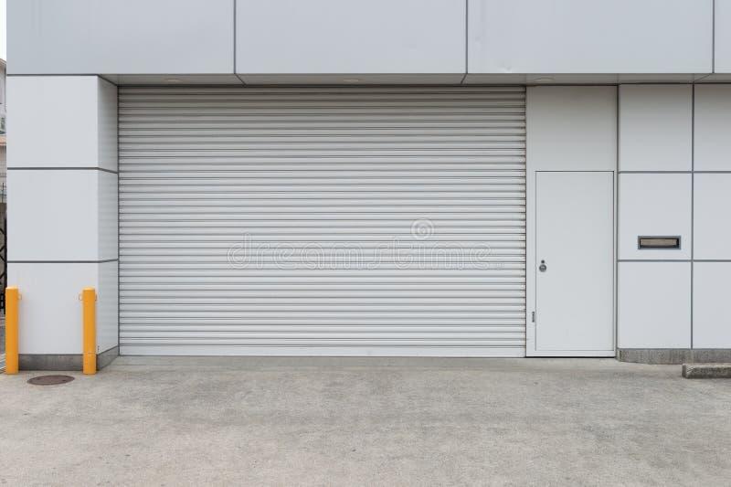 Een close-upschot van de automatische die deur van de metaalrol in fabriek, opslag, garage, en industrieel pakhuis wordt gebruikt stock foto's