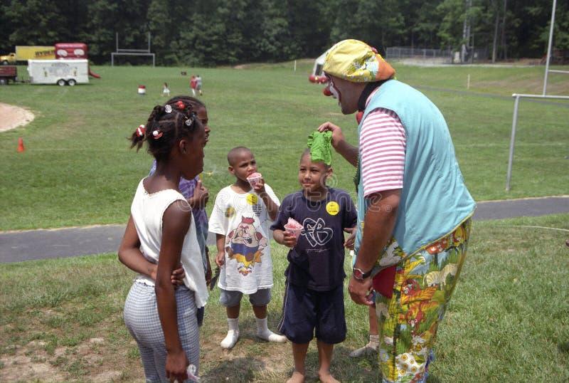 Een clown spreekt aan verscheidene kleine kinderen royalty-vrije stock fotografie