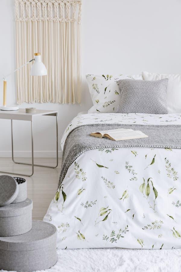 Een comfortabel binnenland van de pastelkleurslaapkamer met een bed gekleed in groene installaties op witte linnen en kussens War royalty-vrije stock foto's