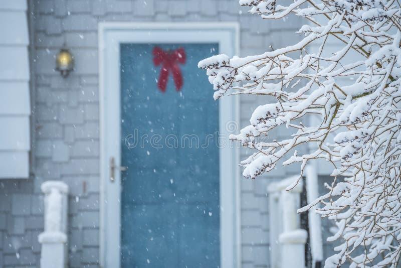 Een comfortabele deur en een portiek van een plattelandshuisje tijdens een sneeuwval stock foto's