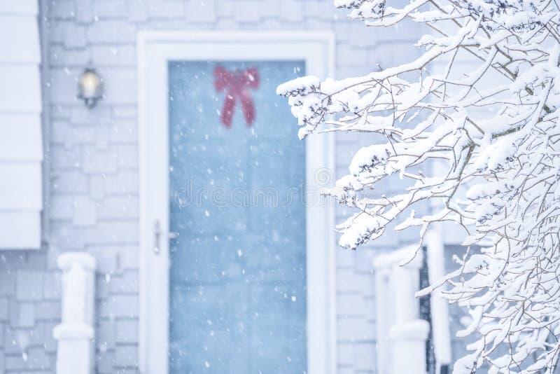 Een comfortabele deur en een portiek van een plattelandshuisje tijdens een sneeuwval royalty-vrije stock fotografie