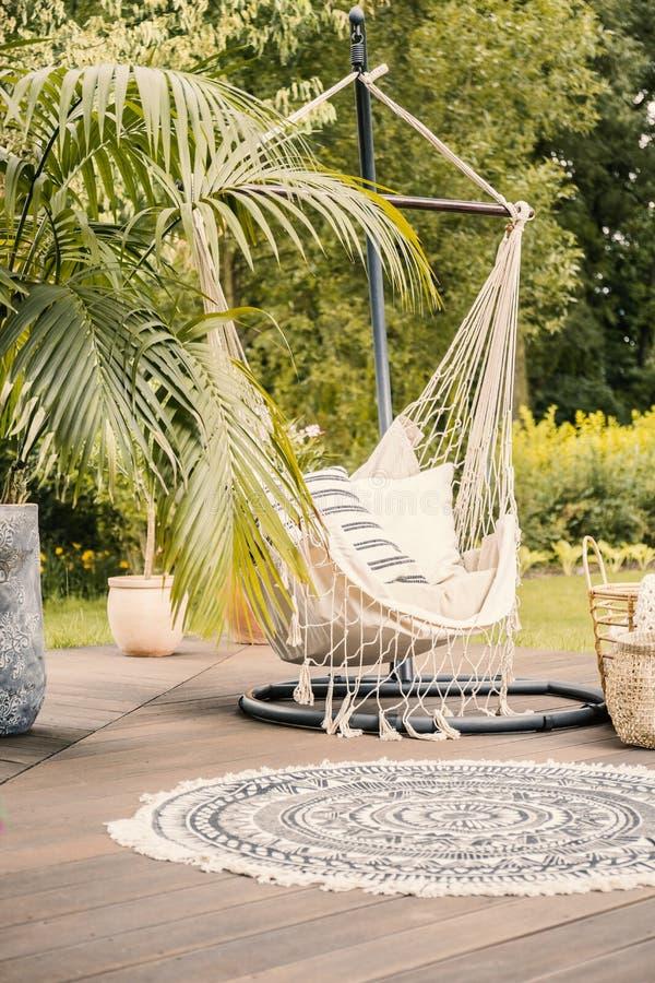 Een comfortabele hangmat met hoofdkussens op een dek in een groene tuin tijdens s stock afbeeldingen