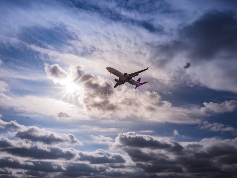 Een commercieel straaldielijnvliegtuig gedeeltelijk tegen de zon wordt gesilhouetteerd royalty-vrije stock foto's