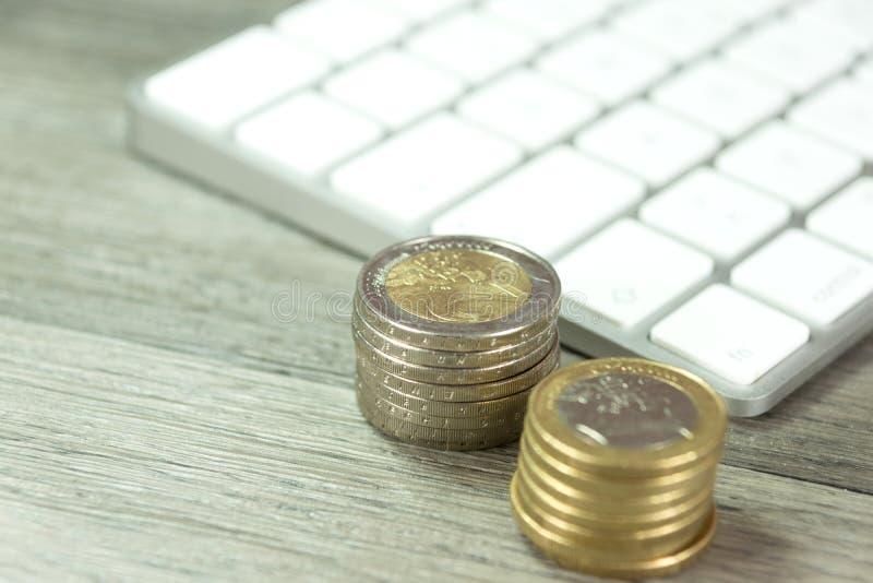 Een computer en een euro geldmuntstuk stock foto's