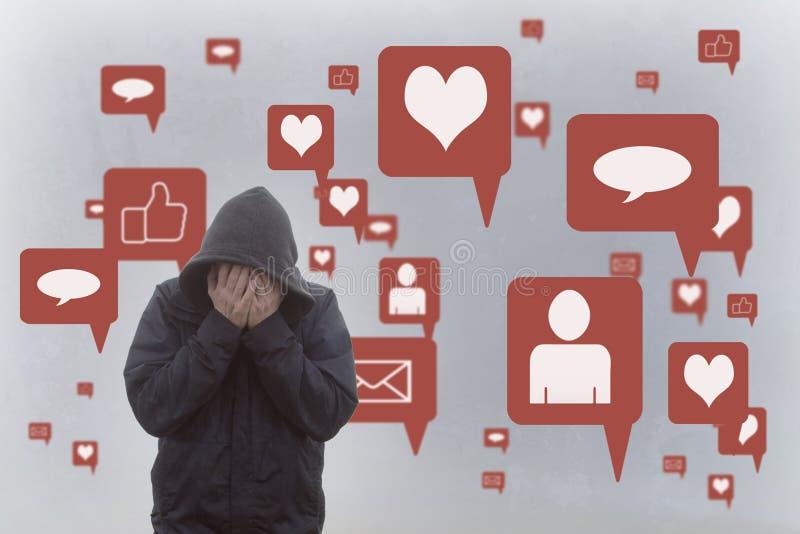 Een concept de negatieve gevolgen van sociale media Een mens die met een kap zijn hoofd in zijn handen houden Met het sociale med stock foto's