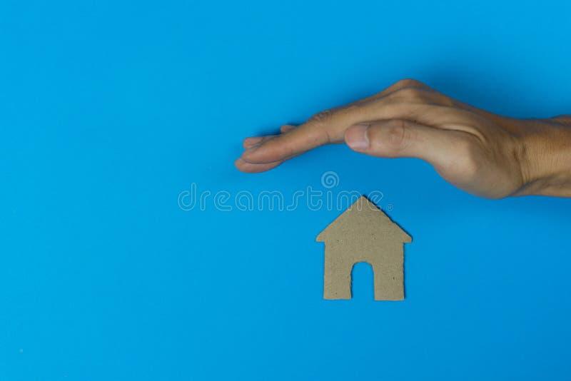 Een concept van de bezitsverzekering Een mensenhand beschermt een plattelandshuisje gemaakt door document op blauwe achtergrond s royalty-vrije stock afbeelding