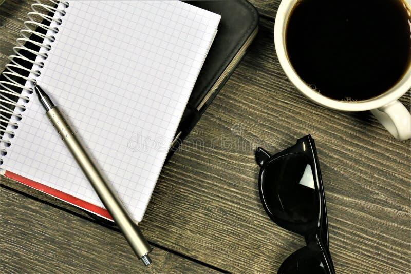 Een conceptenbeeld van een Notitieboekje met glazen, koffie en een bloem royalty-vrije stock fotografie