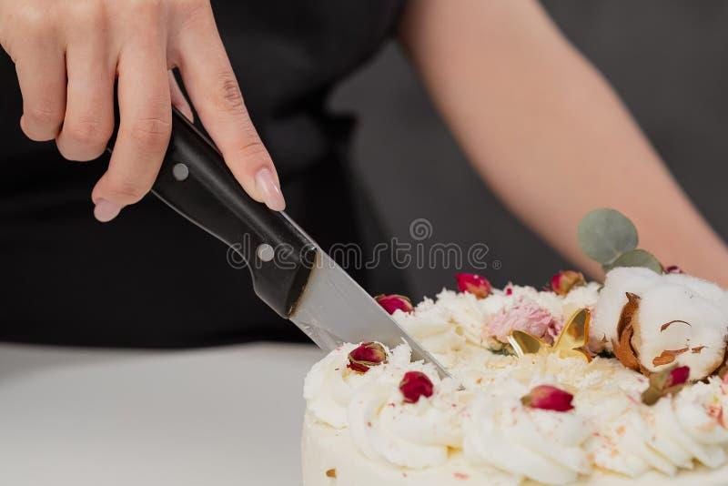 Een condater snijdt een mooie verse verfraaide witte cake met een groot mes royalty-vrije stock foto