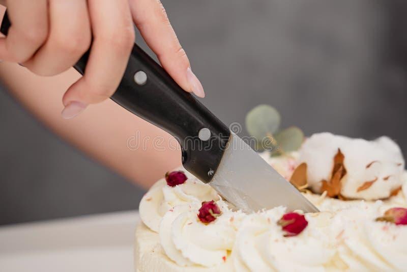 Een condater snijdt een mooie verse verfraaide witte cake met een groot mes royalty-vrije stock afbeeldingen