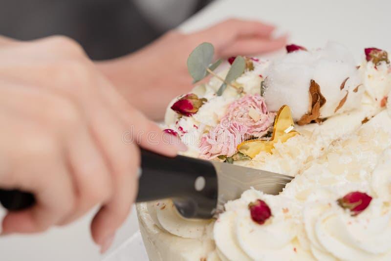 Een condater snijdt een mooie verse verfraaide witte cake met een groot mes stock fotografie