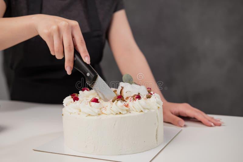Een condater snijdt een mooie verse verfraaide witte cake met een groot mes royalty-vrije stock fotografie
