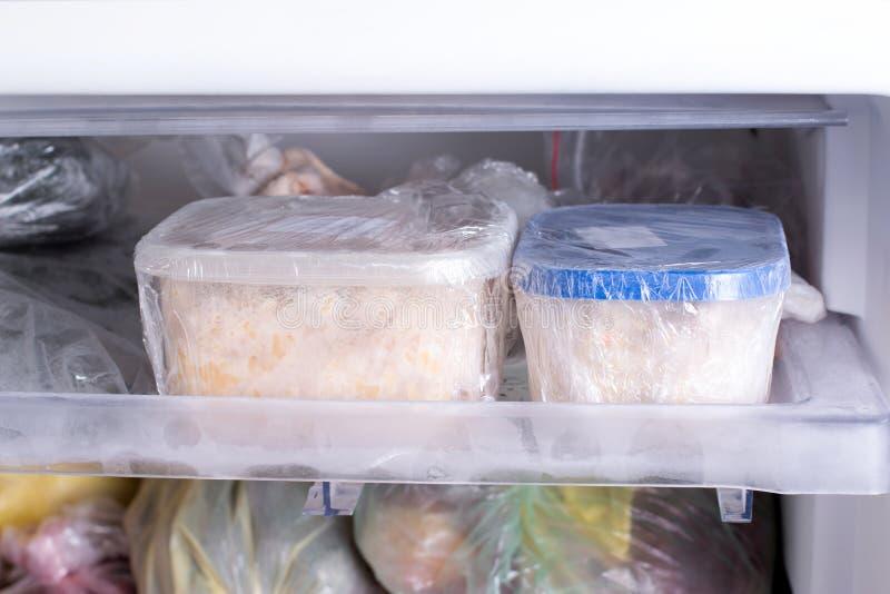 Een container met voedsel in de diepvriezer Een diepvriezer met kip, soep en divers bevroren voedsel wordt ingepakt dat royalty-vrije stock foto's