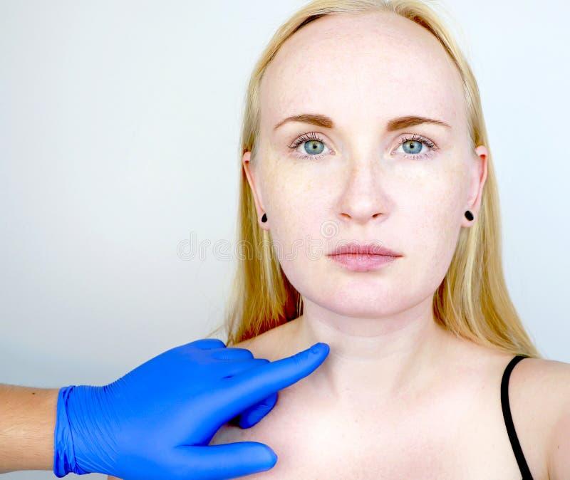 Een cosmetologist bereidt de patiënt voor chirurgie voor: contourplastieken van de hals, mesotherapy of botulinum therapie Rimpel stock foto