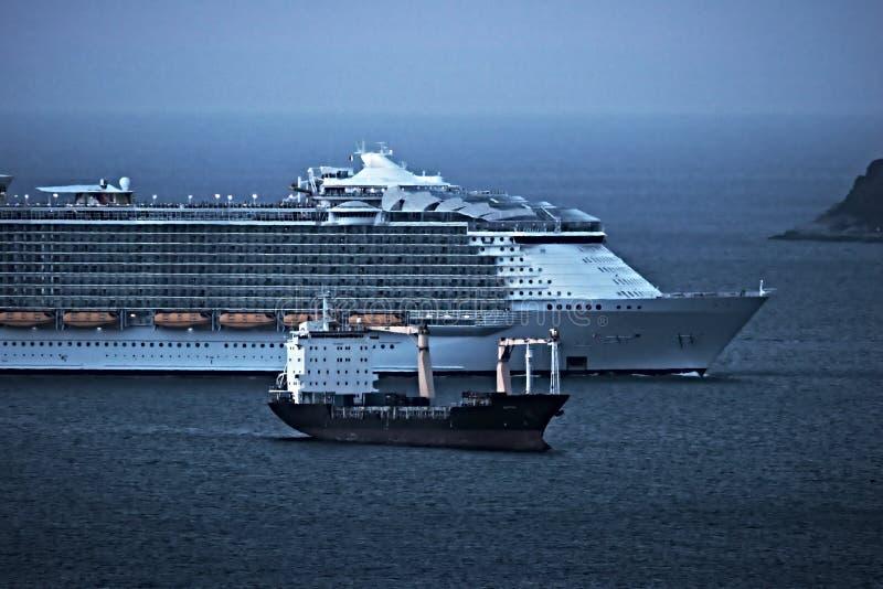 Een cruiseschip in vergelijking met een koopvaardijschip Golf van Laspezia Itali? stock afbeeldingen