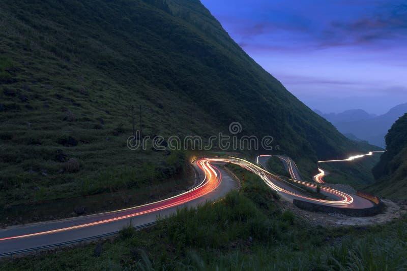 Een curvy weg door de grasrijke heuvels bij schemering stock afbeeldingen