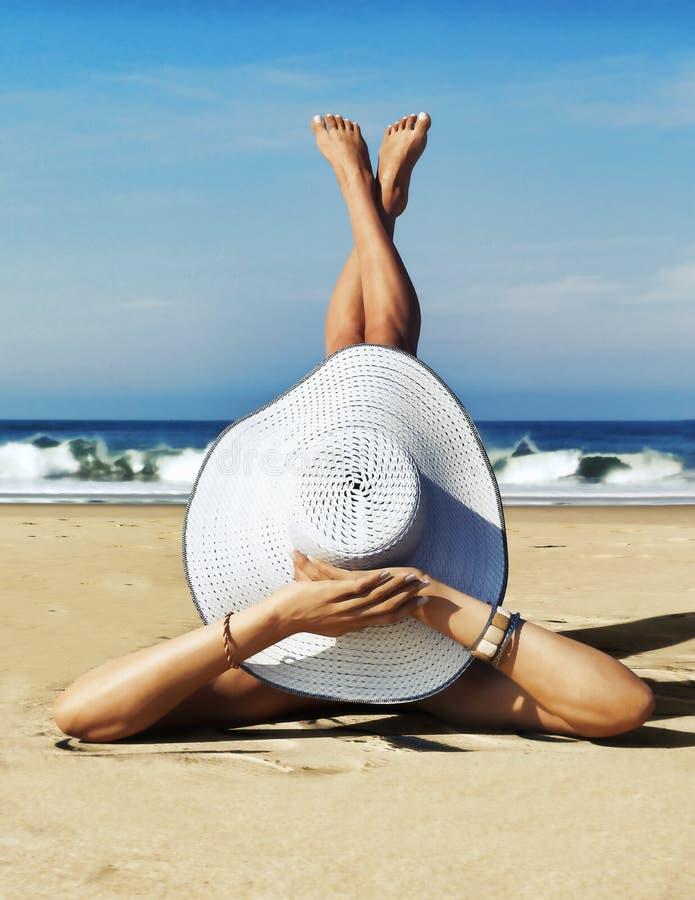 Een dag bij het Strand Leuk sierlijk wijfje die een witte tweedelige bikini en strohoed dragen die van de zon genieten bij het st royalty-vrije stock foto