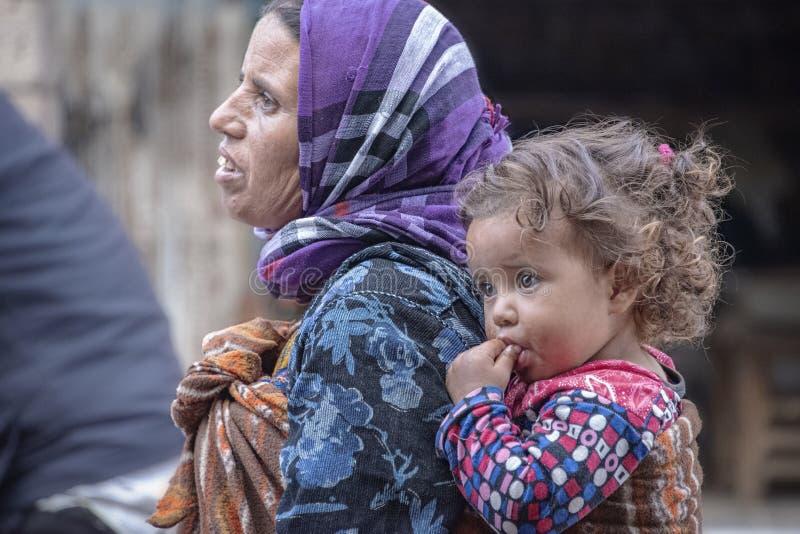 Een dakloze bedelaarsvrouw loopt door stad met een jong meisjeskind dat op haar terug wordt vervoerd royalty-vrije stock afbeelding