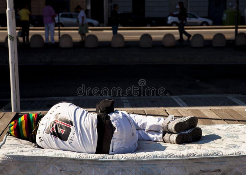 Een dakloze persoon slaapt op de straat Vluchtelingen van Afrika aan de straten van Genua, Italië royalty-vrije stock foto's