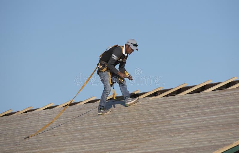 Een dakwerkarbeider met elektrische boor stock foto's