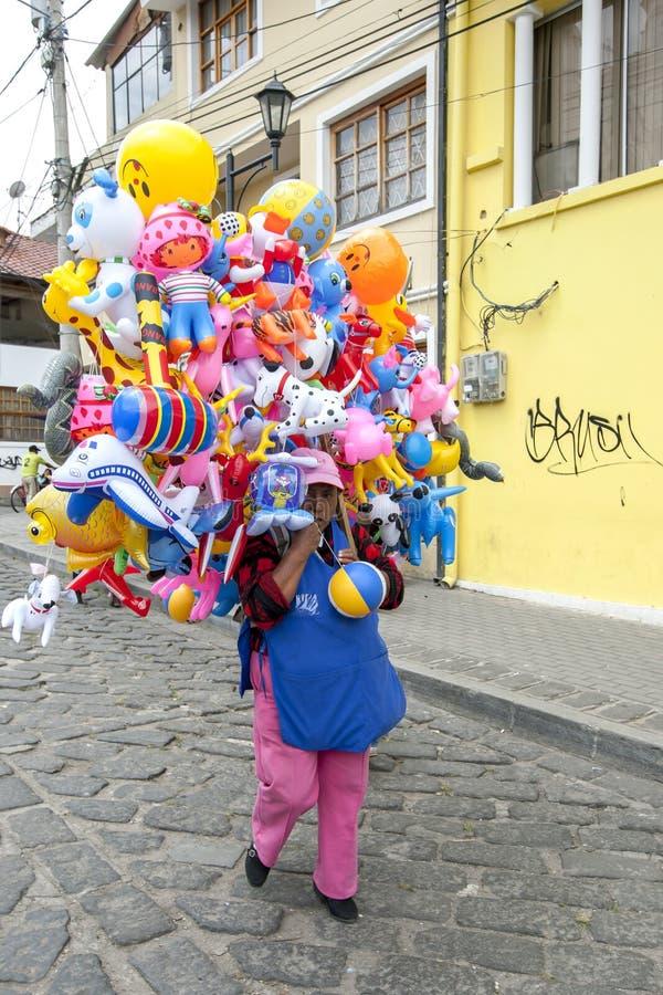 Een dame die van Zuidenameican plastic speelgoed verkopen loopt onderaan een straat in Quinche in Ecuador stock afbeelding