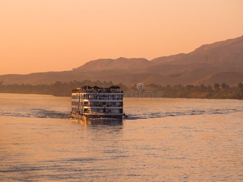 Een de cruiseboot van riviernijl bij zonsondergang stock afbeelding