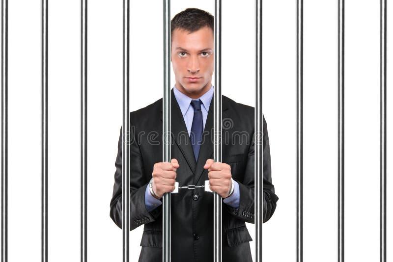 Een de handboeien om:doen zakenman in de staven van de gevangenisholding royalty-vrije stock afbeelding