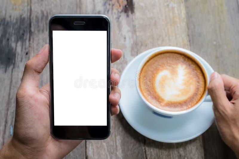 Een de holdingssmartphone van de mensenhand met hete latte, koffiekop op houten bureau in koffiewinkel Smartphone met het lege sc royalty-vrije stock afbeelding