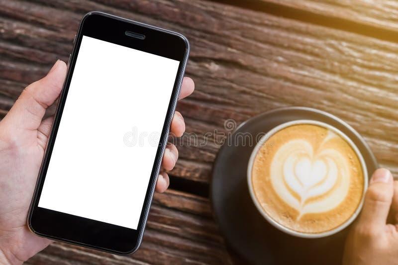 Een de holdingssmartphone van de mensenhand met hete latte, koffiekop streeft na royalty-vrije stock afbeelding