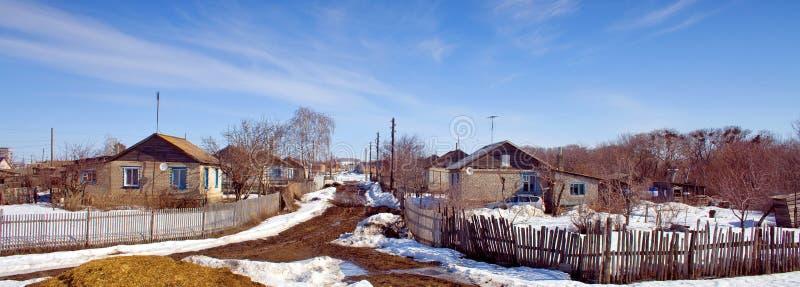 Een de Lente zonnige dag van de dorpsstraat wanneer de sneeuw begint te smelten royalty-vrije stock foto