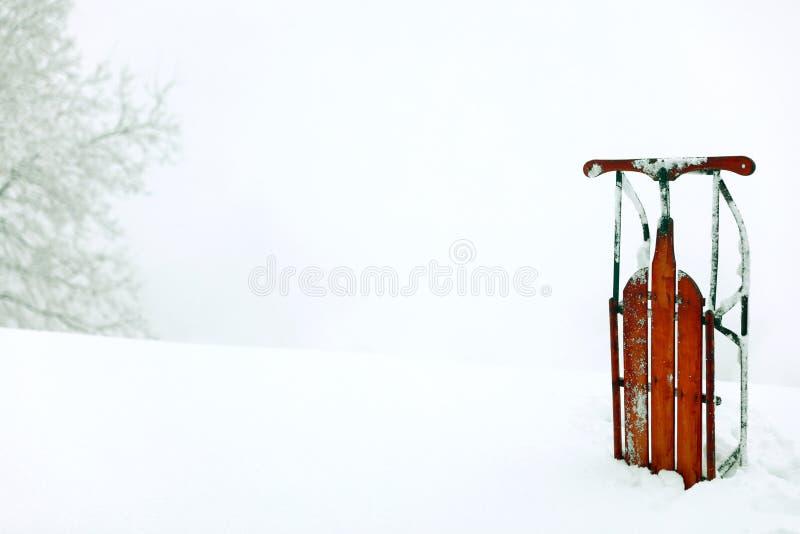 Een de scèneachtergrond van de de wintersneeuw met een rode uitstekende rechte slee royalty-vrije stock afbeelding