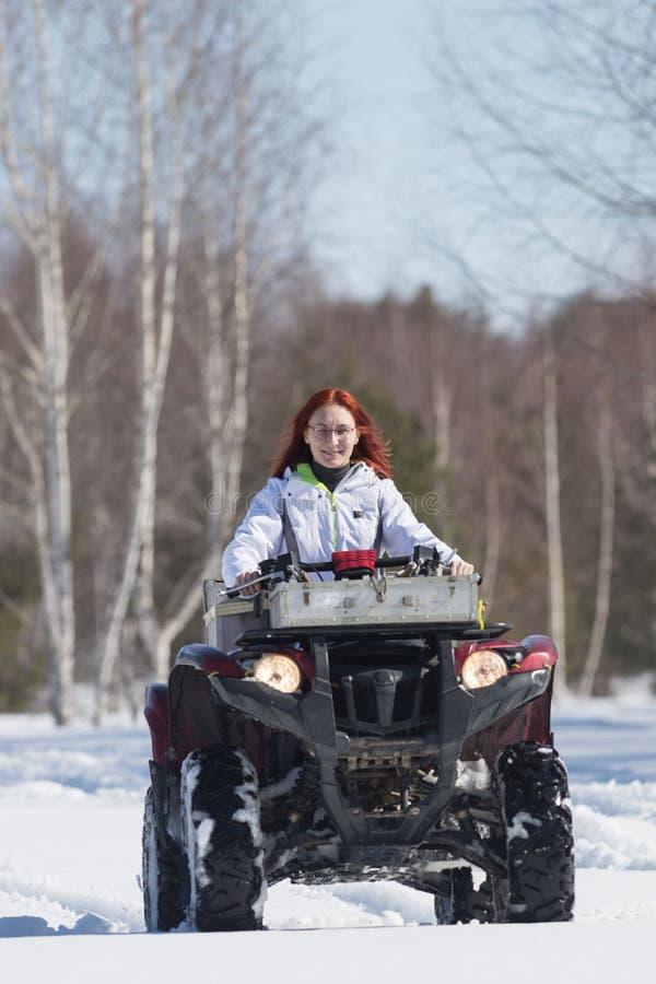 Een de winter bosa vrouw met gemberhaar die grote rode sneeuwscooter berijden en de sneeuw overwinnen royalty-vrije stock afbeeldingen