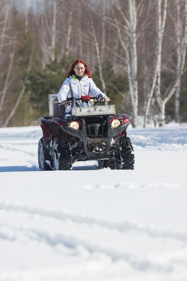Een de winter bosa vrouw met gemberhaar het berijden sneeuwscooter en het overwinnen van de sneeuw stock afbeelding