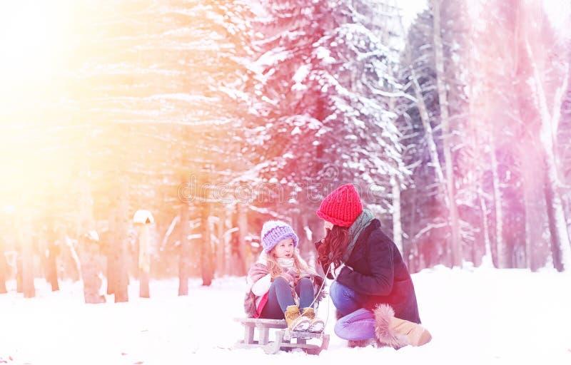 Een de wintersprookje, een jonge moeder en haar dochter berijden een slee royalty-vrije stock foto