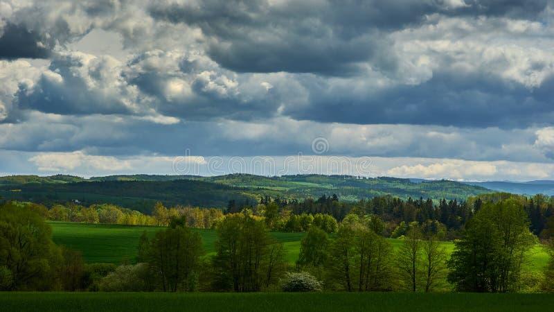 Een de zomer heuvelig landschap met donkere, zware wolken die in de hemel stromen royalty-vrije stock foto's
