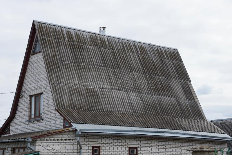 Een deel van een baksteenhuis met een venster in de zolder onder een grijs leidak stock afbeelding