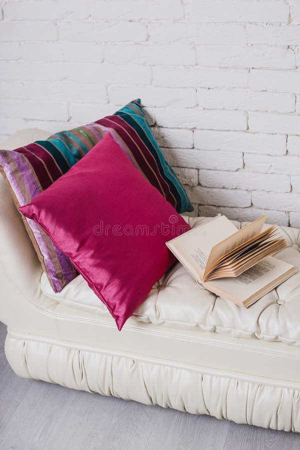 Een deel van binnenland met laag en decoratieve hoofdkussens, witte houten lijst met boeken op het stock foto's