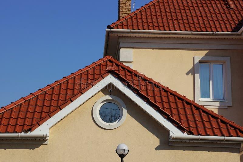 Een deel van een bruin huis met een rond venster in zolder en rood betegeld dak tegen de blauwe hemel stock foto's