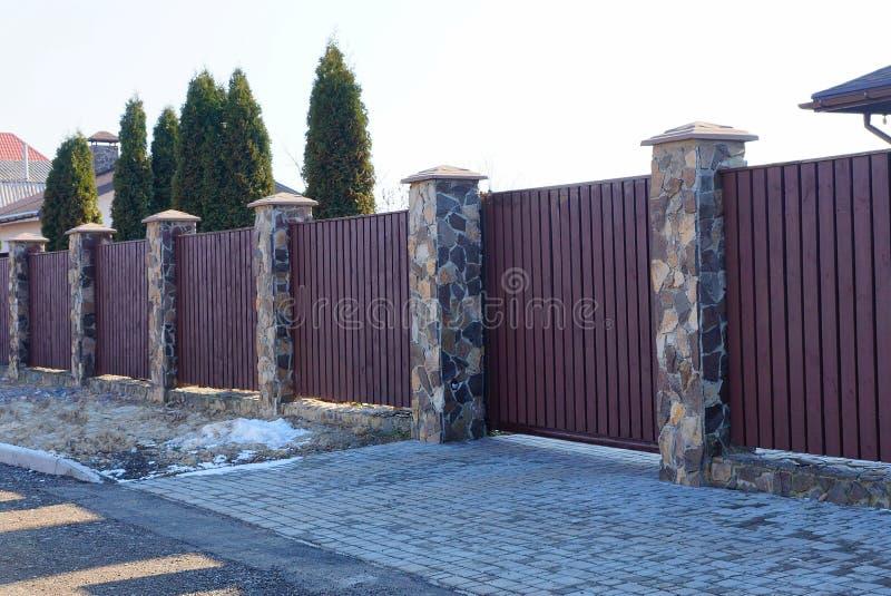 Een deel van een bruine omheining met een poort die van houten planken en stenen buiten wordt gemaakt royalty-vrije stock foto's