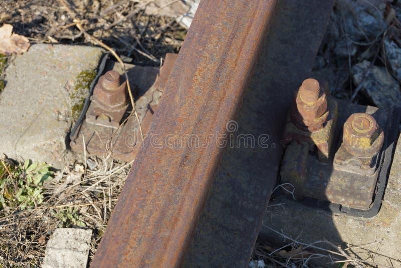 Een deel van bruine staalsporen en roestige bouten en noten op de spoorweg royalty-vrije stock fotografie