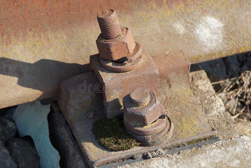 Een deel van bruine staalsporen en roestige bouten en noten op de spoorweg royalty-vrije stock foto