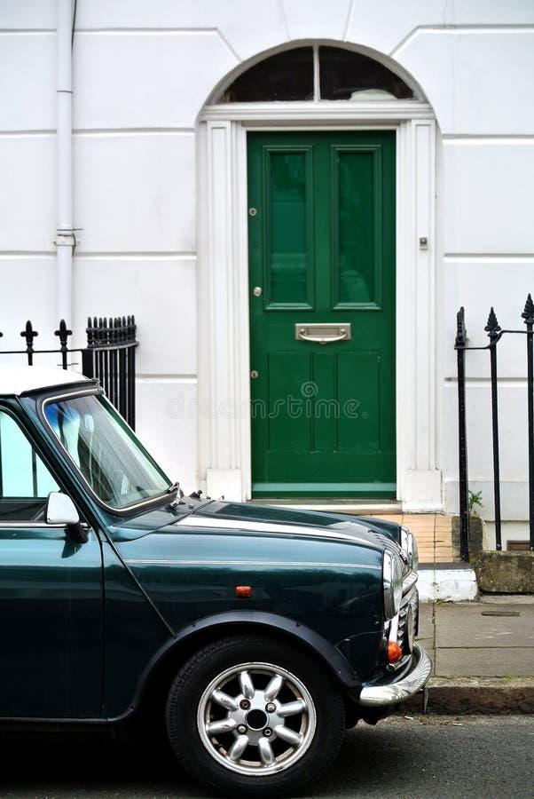 Een deel van een de bouwvoorgevel met groene deur en geparkeerde auto, royalty-vrije stock foto's