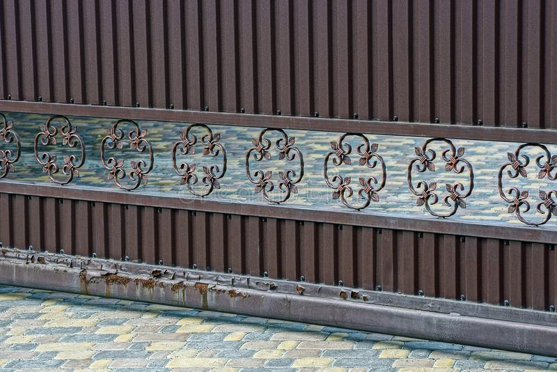 Een deel van de bruine ijzerpoort met een patroon op de straat boven de stoep stock fotografie