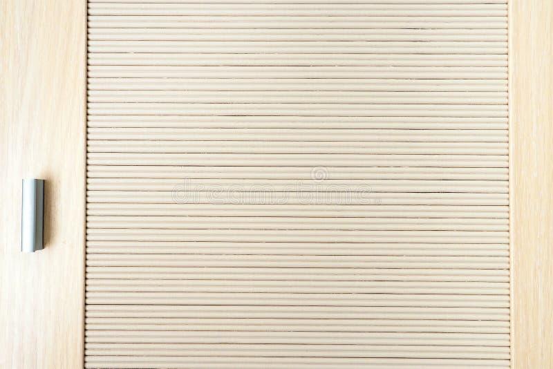 Een deel van de deur van beige houten latjes en handvat, sluit omhoog houten textuur stock foto's
