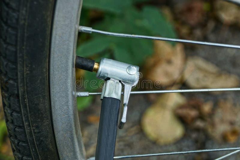 Een deel van de pomp met een slang op het uitsteeksel van het fietswiel royalty-vrije stock afbeelding