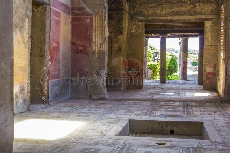 Een deel van de woonkamer met fresko's schilderde op de muren in een geruïneerd huis in Pompei, Napels, Italië De ruïnes van oud  stock fotografie
